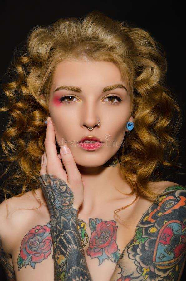 有纹身花刺的迷人的金发碧眼的女人在身体 免版税图库摄影