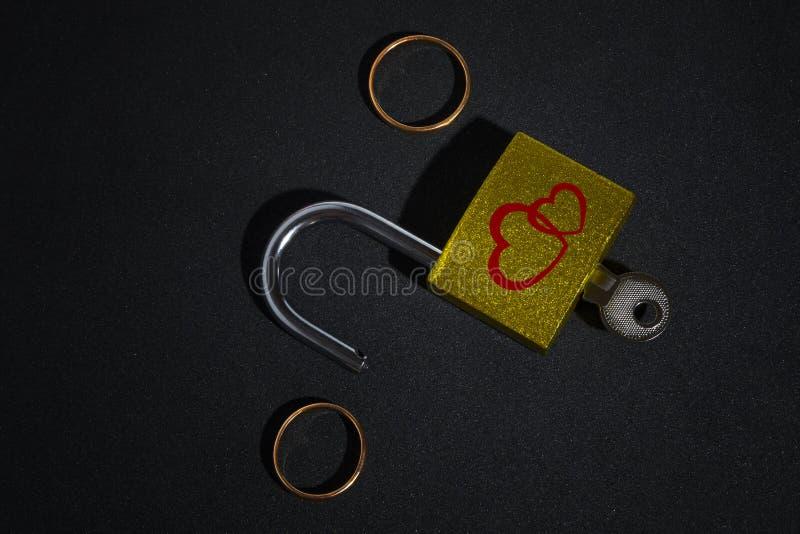 有结婚戒指的开放挂锁在黑背景 免版税库存图片