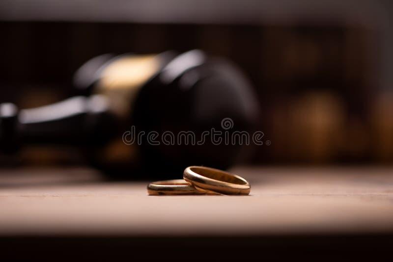 有结婚戒指的法官惊堂木在木桌上 图库摄影