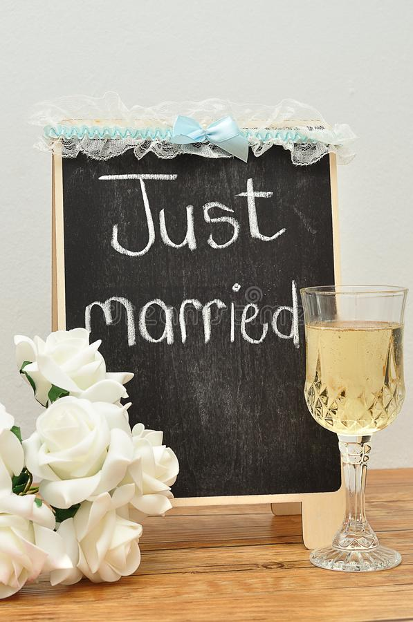 有结婚的一个黑板对此显示了与一杯香槟,一束玫瑰和袜带 免版税库存照片
