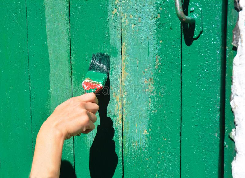有绘老木门的刷子的工作者手 免版税库存照片