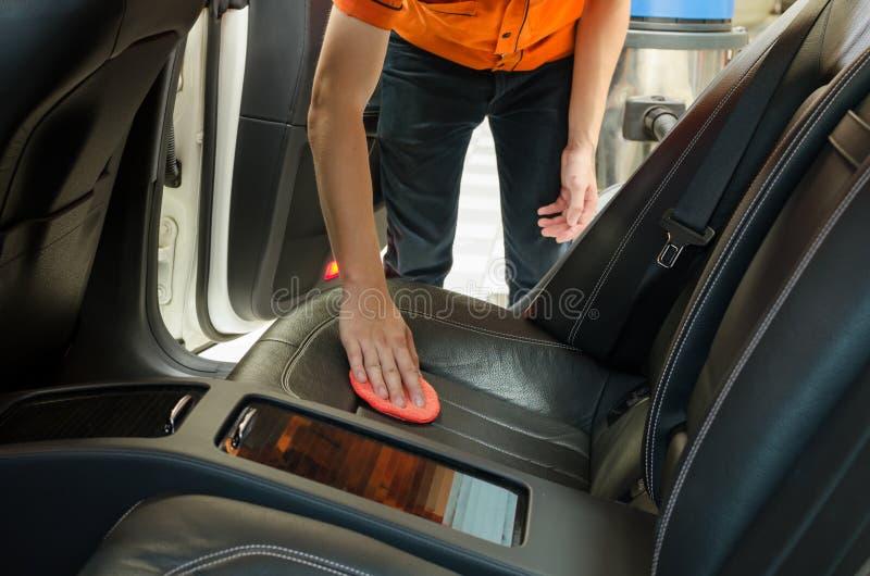 有给内部汽车打蜡的microfiber海绵的手 库存图片