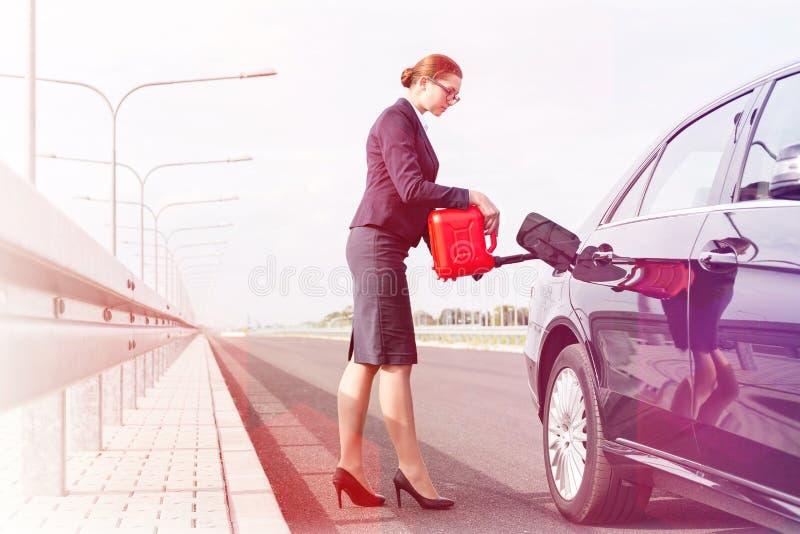 有给在路的罐的女实业家汽车加油反对天空 免版税图库摄影