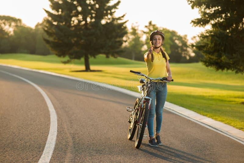 有给赞许姿态的自行车的愉快的女孩 免版税库存照片