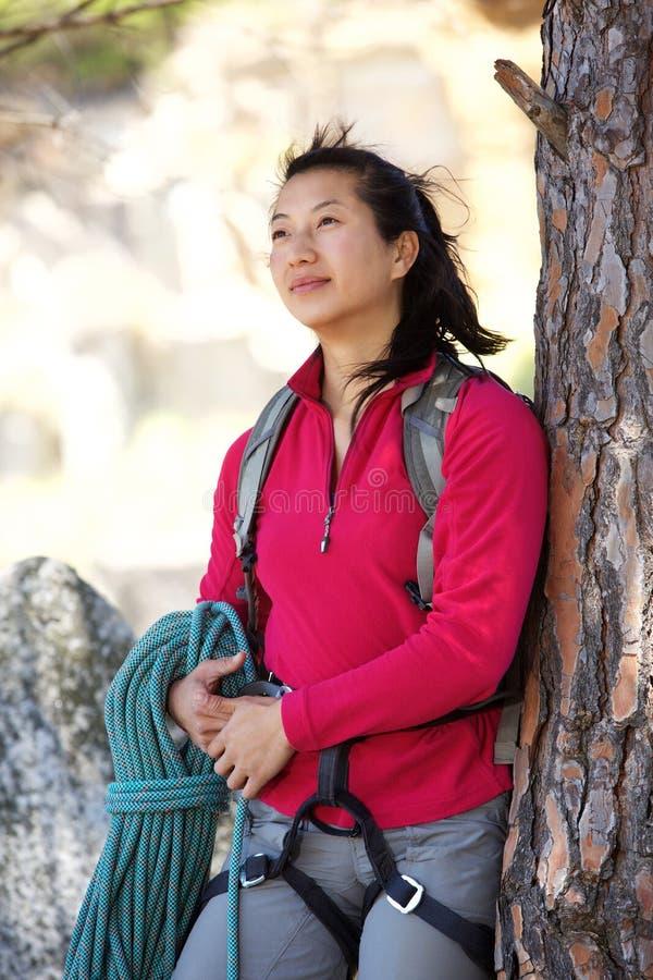 有绳索倾斜的agaisnt树的亚裔妇女远足者 库存图片