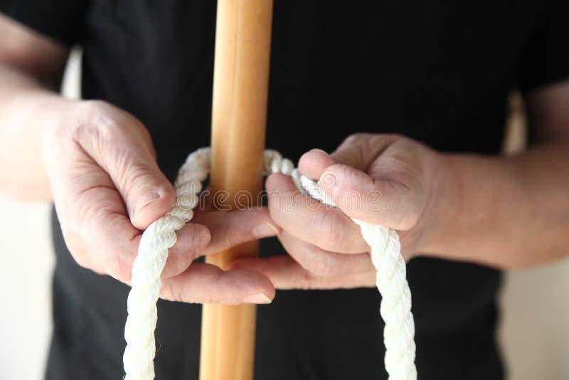 有绳索和木头杆的人 库存图片