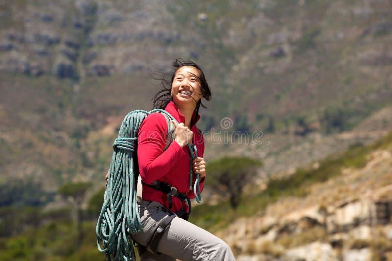 有绳索的微笑的亚裔女性登山人走在山的 免版税库存图片