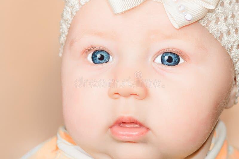 有绷带的新生儿女孩在他的头和蓝眼睛,特写镜头 免版税库存图片