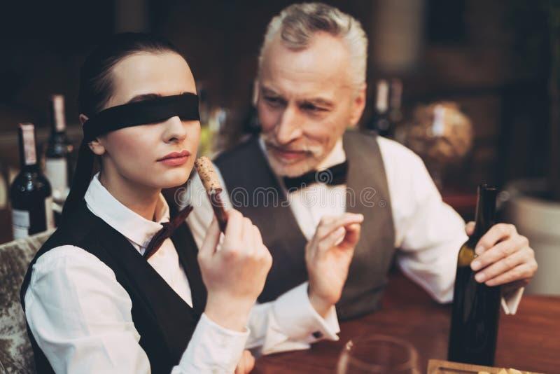 有绷带的老练的斟酒服务员在眼睛嗅从瓶的黄柏酒在拔塞螺旋 免版税图库摄影