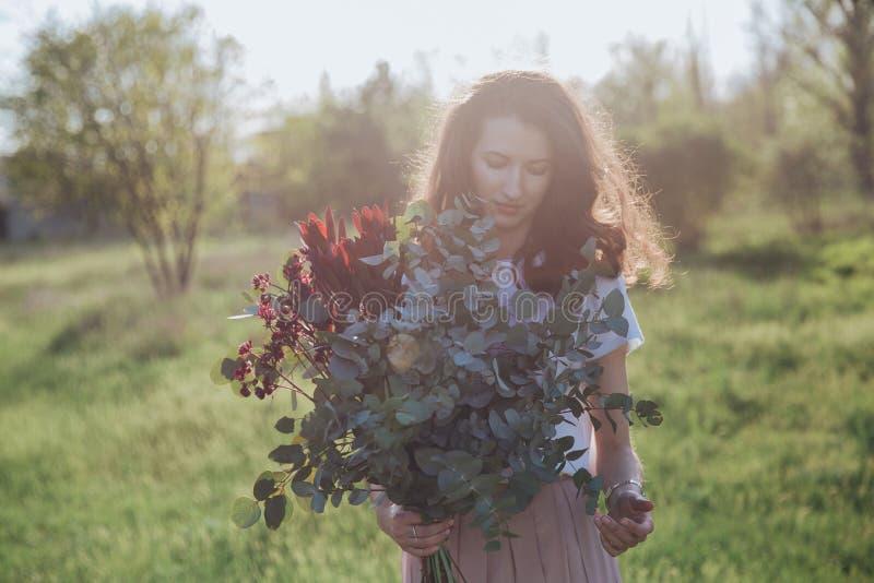 有绿叶花束的葡萄酒女孩在日落背景 免版税库存图片