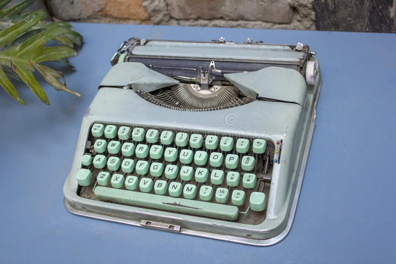 有绿松石绿色按钮的葡萄酒蓝色打字机在与植物的分支的一张桌上站立 库存照片
