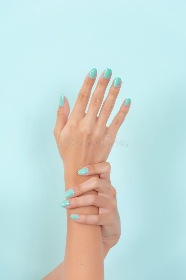 有绿松石颜色修指甲的妇女手在蓝色软的蓝色背景隔绝的秀丽演播室 免版税库存图片