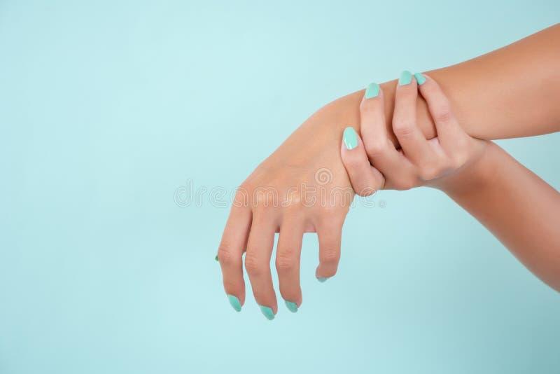 有绿松石颜色指甲油的妇女手在蓝色软的蓝色背景隔绝的秀丽演播室 免版税库存照片
