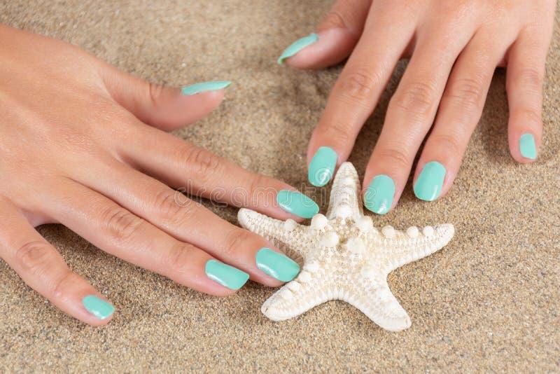 有绿松石颜色的女性手轻轻地指甲油拿着海星和海沙在背景中 库存照片