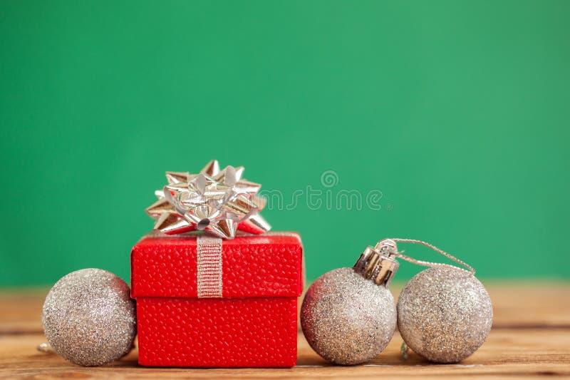 有绿色丝带的红色圣诞节礼物盒和在绿色背景的三个xmas球 免版税库存照片