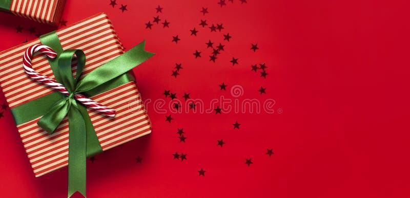 有绿色丝带的,棒棒糖,闪烁星五彩纸屑形式礼物盒在红色背景顶视图平的位置的 假日概念,新 图库摄影