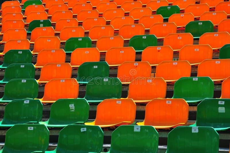 有绿色和橙色塑料位子的正面看台 免版税库存照片