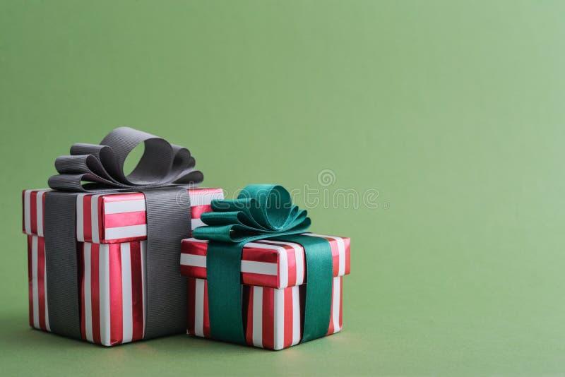 有绿色和灰色丝带的两个红色镶边礼物盒 免版税库存照片