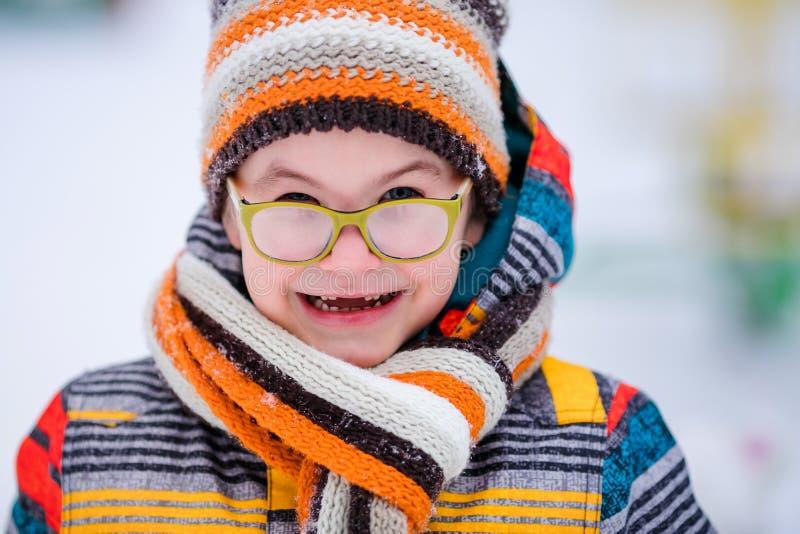 有绿色大玻璃、编织的帽子和围巾的微笑的男孩 背景多雪的冬天 免版税库存图片