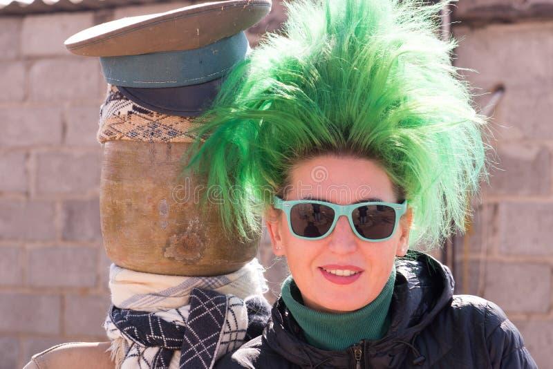 有绿色头发的白种人女孩在村庄房子的仓前空地 库存图片