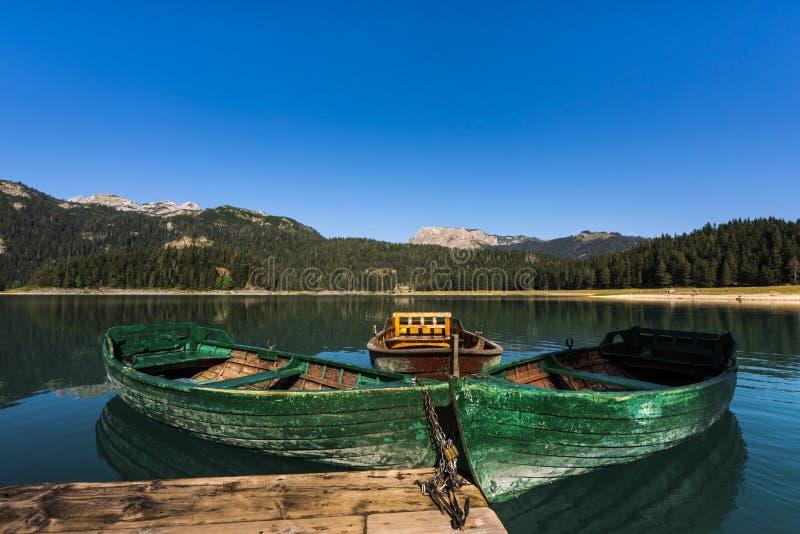 有绿色小船的黑湖在透明的水,黑湖国家公园,黑山中反射了 免版税图库摄影