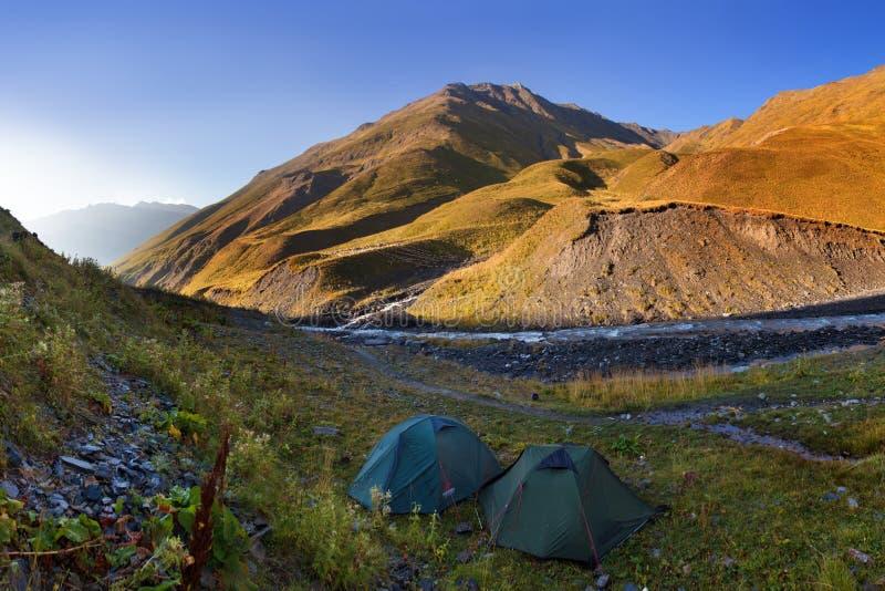 有绿色旅游帐篷的五颜六色的夏天全景在山下的谷在天空蔚蓝下 狂放美丽的山 免版税库存图片