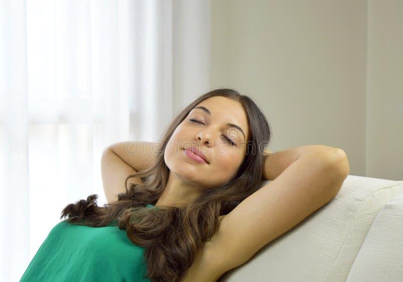 有绿色无袖衫在家放松的微笑的少妇在沙发坐一个沙发在客厅 免版税库存图片