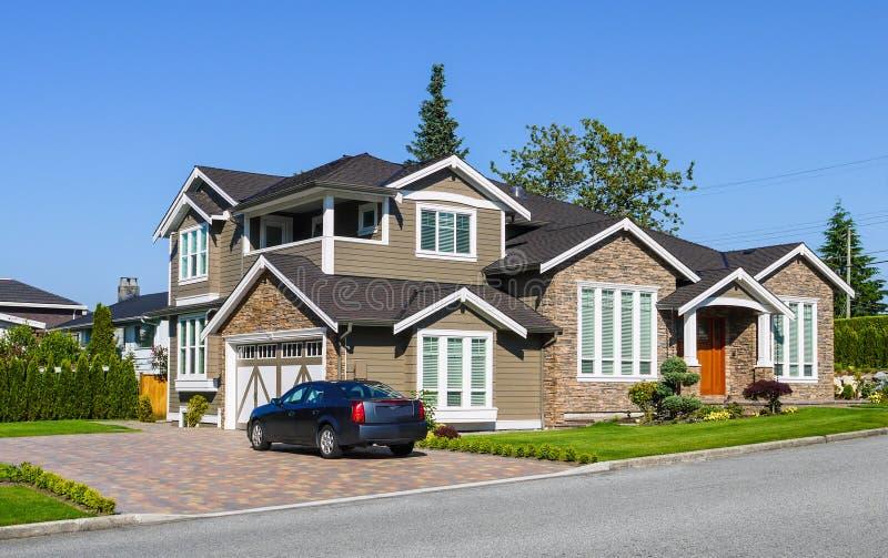 有绿色树篱的豪华住宅房子在前面的旁边和绿色草坪 有双重车库的郊区家庭停放的房子和汽车 免版税图库摄影
