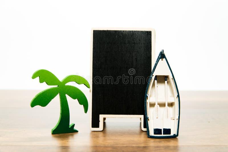 有绿色棕榈树和白色小船的空白的木黑人委员会 库存图片