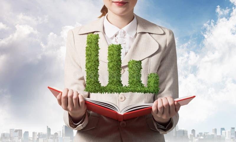 有绿色植物形状的财政图表的妇女 图库摄影
