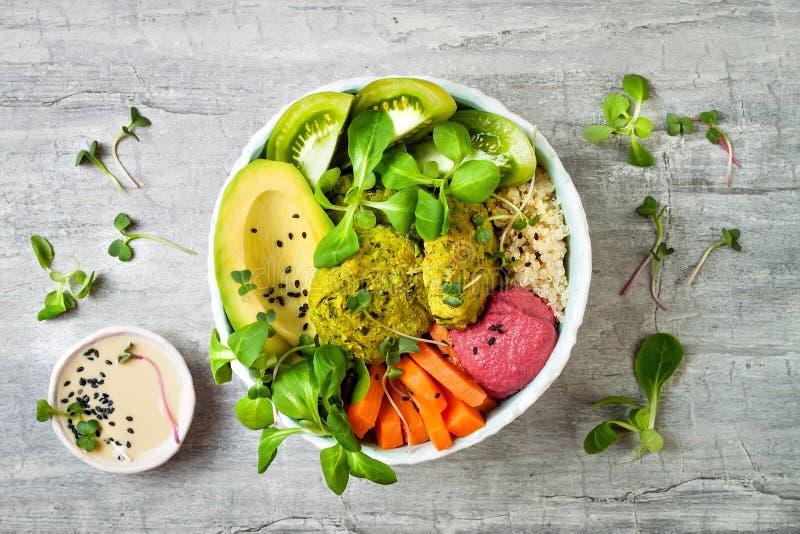 有绿色沙拉三明治的中东样式菩萨碗,奎奴亚藜、胡桃南瓜、蕃茄、鲕梨、甜菜根hummus和tahini调味 免版税图库摄影
