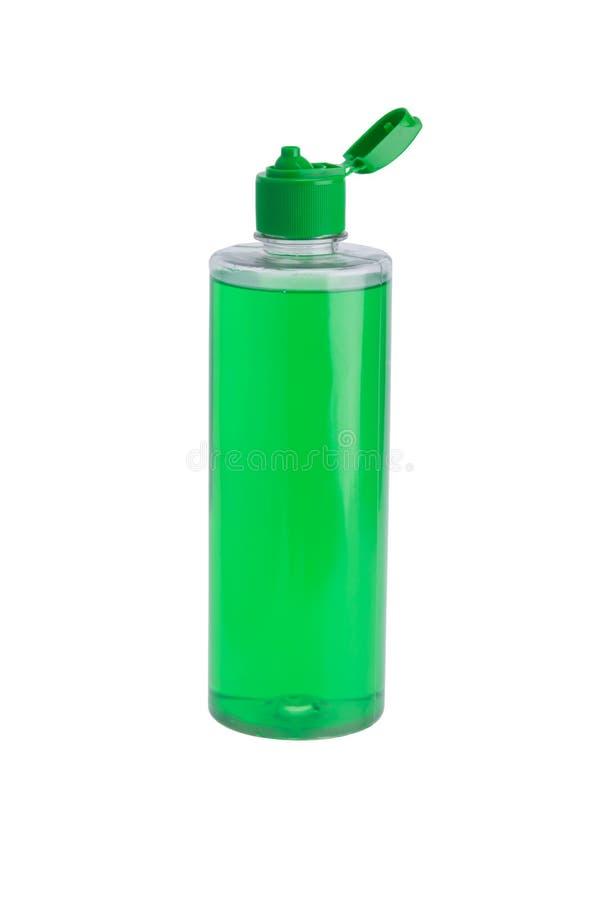 有绿色液体的,香波透明瓶,开放,在白色背景 免版税库存照片