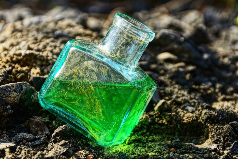 有绿色液体立场的一个小玻璃状老瓶在灰色地面外部 免版税库存图片