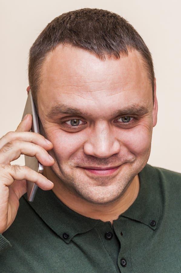 有绿色球衣谈的电话的愉快,微笑的人 免版税图库摄影