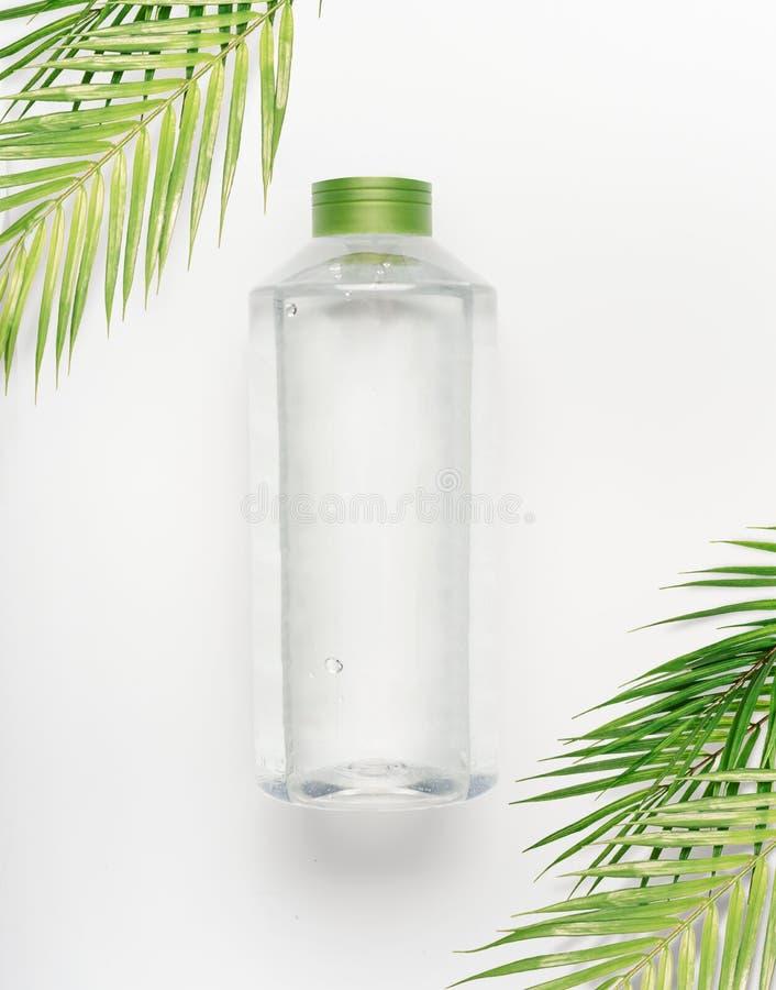有绿色盒盖的透明液体瓶在与热带棕榈叶的白色书桌背景 免版税库存图片