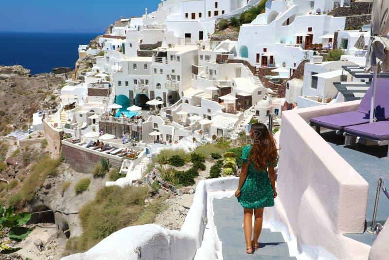 有绿色礼服的年轻时尚妇女和走在台阶在Oia,圣托里尼 女性旅行游人她的暑假 图库摄影