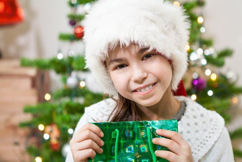有绿色礼物袋子的暴牙的微笑的逗人喜爱的女孩,看照相机圣诞前夕 库存图片
