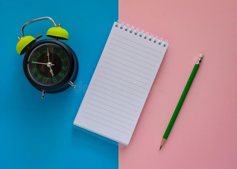 有绿色铅笔和闹钟的开放笔记本在桃红色和蓝纸背景 库存照片