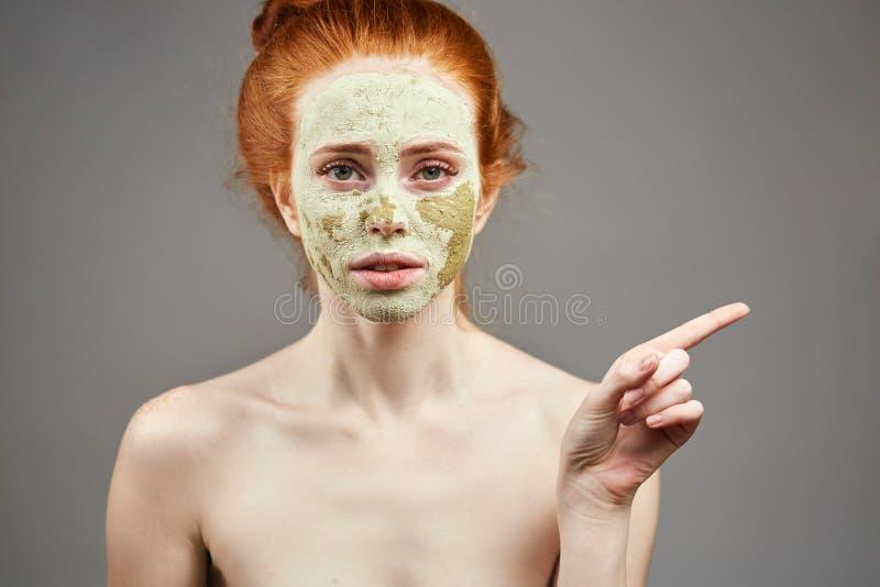 有绿色黏土面具的宜人的女孩指向某处的 免版税图库摄影