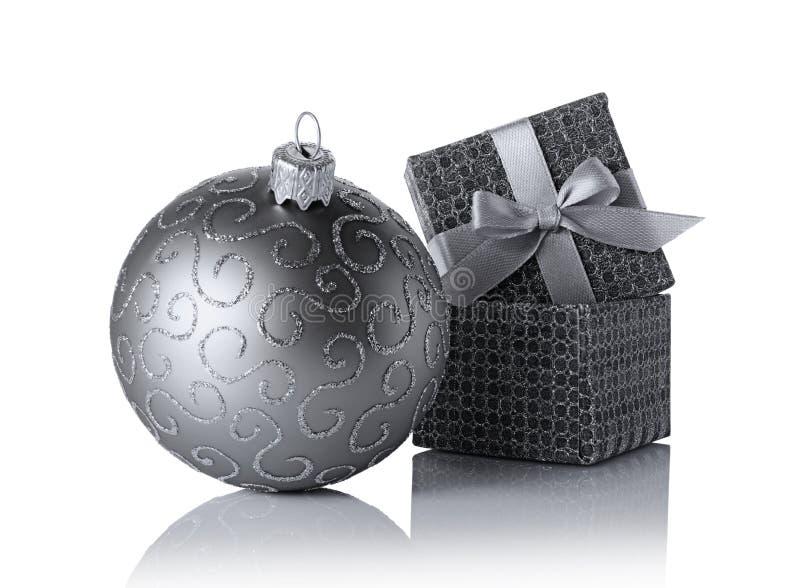 有缎弓的银色经典礼物盒和玻璃与闪烁的样式的圣诞节球 免版税库存照片