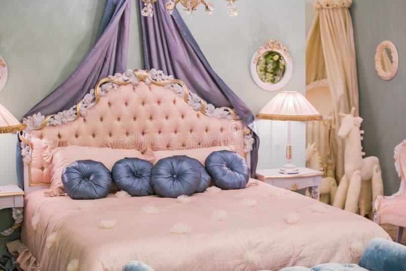 有缎的桃红色一点公主室把枕在,床头灯,床头柜,在墙壁上的框架 豪华富有的卧室内部 免版税库存照片