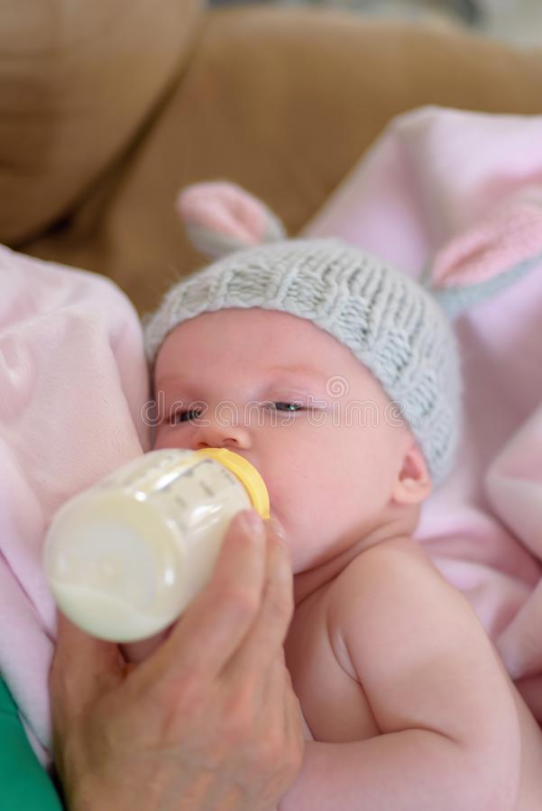 有编织兔宝宝得到一个瓶牛奶的耳朵帽子的新出生的婴孩 免版税库存照片
