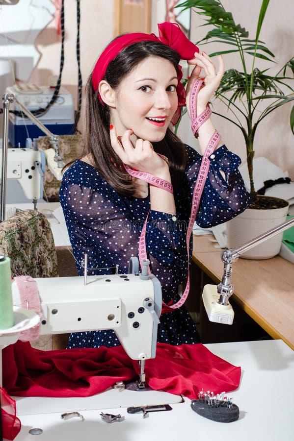 有缝纫机和测量的磁带的滑稽的相当年轻画报妇女 免版税库存图片
