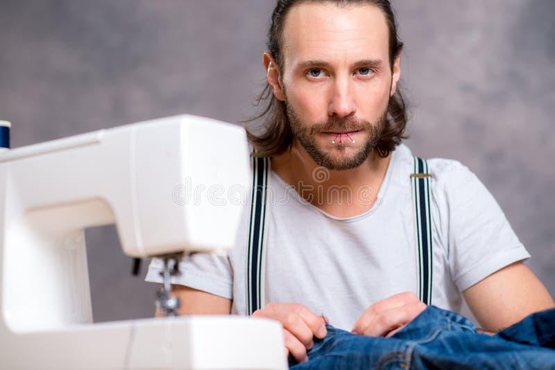 有缝纫机的年轻人裁缝 免版税图库摄影