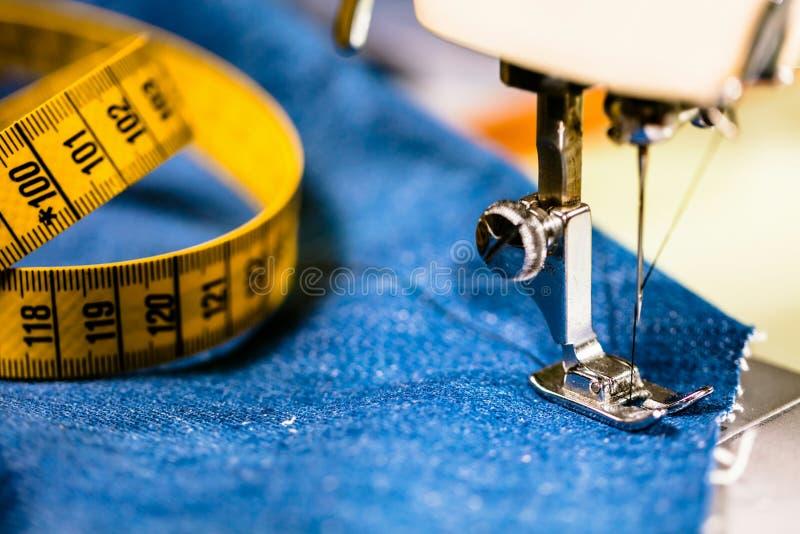 有缝纫机的缝合的牛仔布牛仔裤 由缝纫机的修理牛仔裤 改变牛仔裤,吊边一条牛仔裤,手工制造 免版税库存照片
