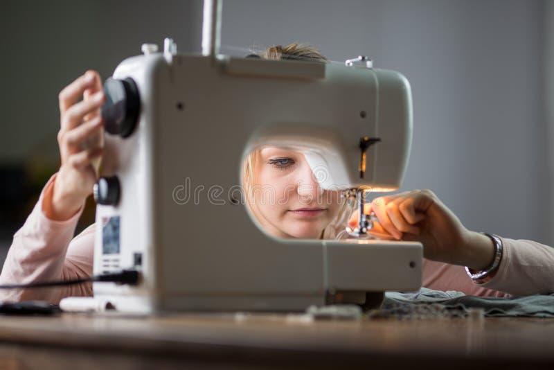 有缝纫机的美丽的少妇缝合的衣裳 图库摄影
