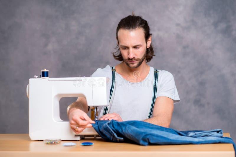 有缝纫机的年轻人裁缝