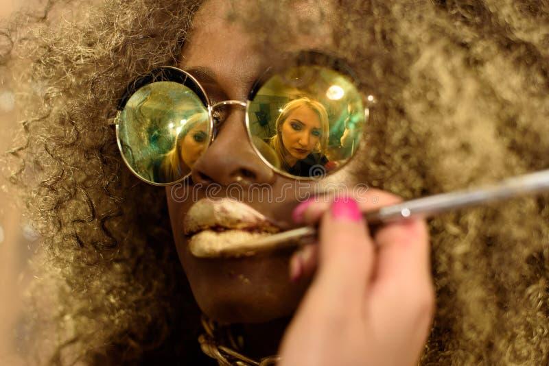 有缨子的白肤金发的艺术家绘画金嘴唇在非洲的太阳镜反射了时尚或黑美国模型佩带明亮 库存照片