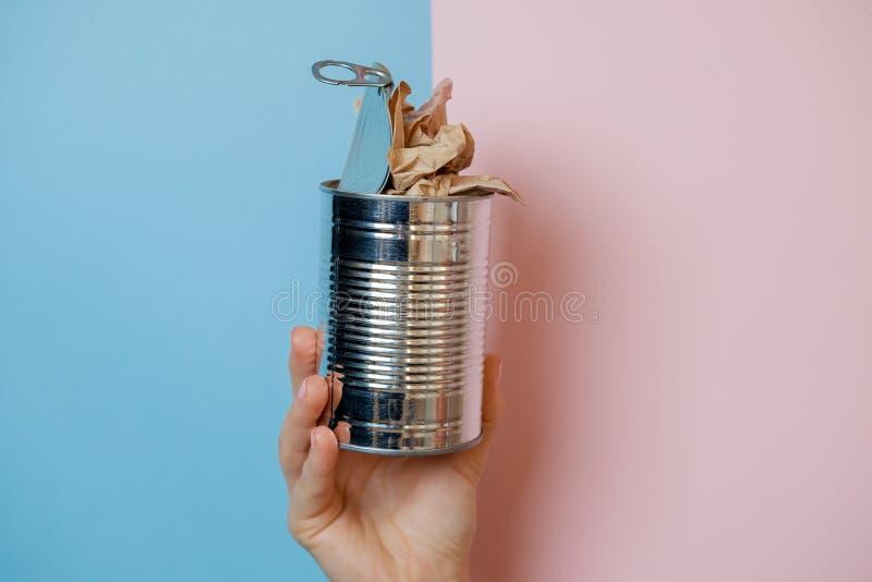 有罐头的手在桃红色背景 分开的无用单元收集 免版税图库摄影