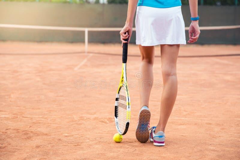 有网球拍的女性腿 免版税库存照片